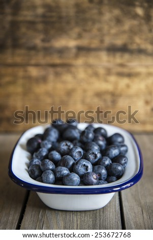 Blueberries in rustic setting with old wooden background
