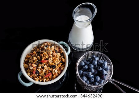Blueberries in steel cup stainer, granola in an enamel white and blue bowl and yogurt in a glass jug on black background directly from above