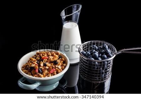 Blueberries in steel cup stainer, granola in an enamel white and blue bowl and yogurt in a glass jug on black background from side high angle