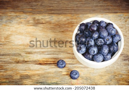 blueberries in the white bowl on a dark wood background. toning. selective focus on the middle of blueberries