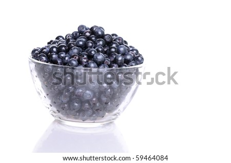 Blueberries in transparent glass dish with soft shadow on white background - stock photo
