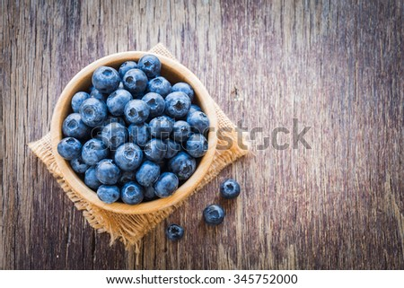 Blueberries in wooden bowl on wooden table background