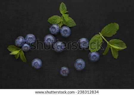 Blueberries isolated on black background with green mint leaves. Healthy fresh seasonal fruit eating. - stock photo