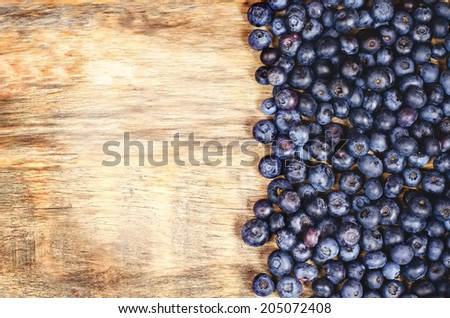 blueberries on a dark wood background. toning. selective focus on the left middle blueberries - stock photo