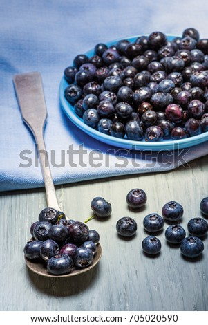 Blueberries on a wooden board in a blue plate and in a old silver spoon with a blue napkin