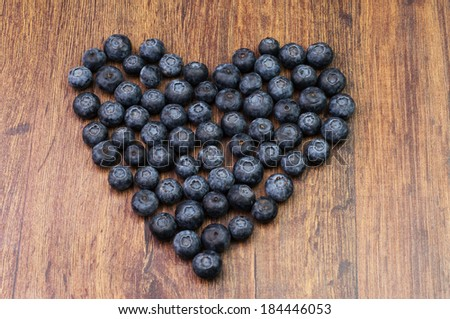 Blueberries on a wooden surface in a shape of a heart