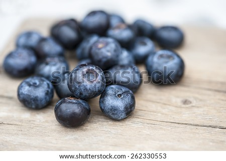 Blueberries on wooden table; focus on single blueberry (Shallow DOF)