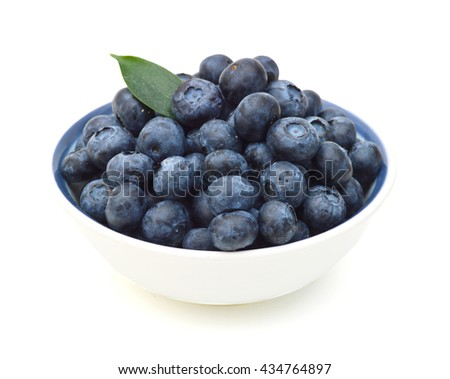 Blueberries with leaves in bowl on white background.
