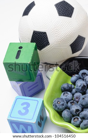 Blueberries with wooden blocks and soccer ball - stock photo