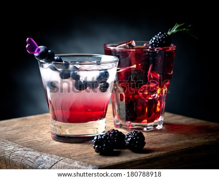 Blueberry and blackberry cocktails on a wooden board - stock photo