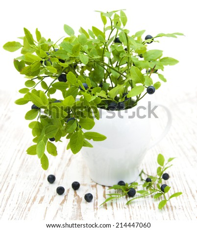 Blueberry branch in a vase on a wooden table