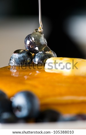 Blueberry butter pancake with honey/ maple syrup flowing down closeup shoot - stock photo