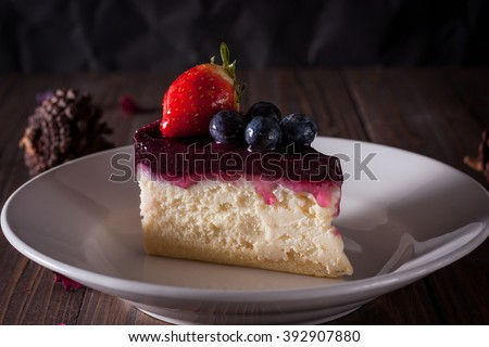 Blueberry cheesecake decorate with pine-corn and dry flower on wood board