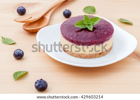 Blueberry cheesecake with fresh mint leaves on wooden background. Selective focus depth of field.