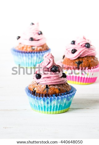 Blueberry Cupcakes decorated with whipped cream frosting and fresh blueberries on a white background. Blueberry muffins with oat flakes.