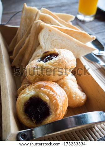 Blueberry danish and bread on basket for breakfast - stock photo
