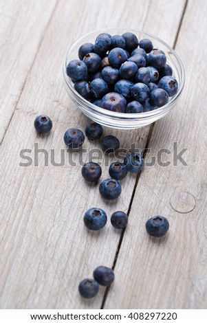 Blueberry in glass bowl on wooden table background