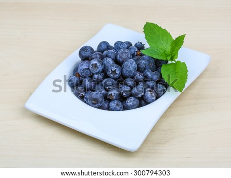 Blueberry in the bowl with mint leaves on wood background