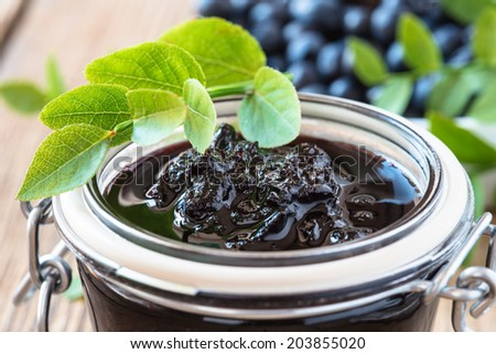 Blueberry jam in glass jar on wooden table and fresh berries. Homemade preserves - stock photo