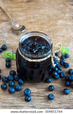 Blueberry jam in jar with berries and leaves over rustic wooden table - stock photo