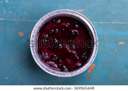Blueberry mini pie on aluminum cups on rustic blue wooden background - stock photo