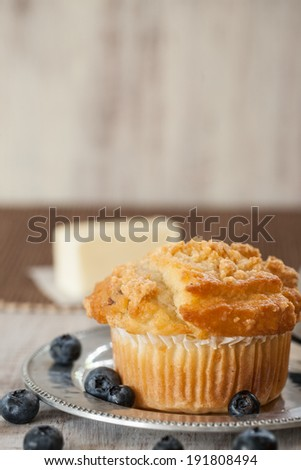 Blueberry muffin breakfast with blueberries scattered about and butter - stock photo
