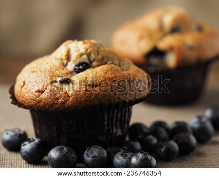 Blueberry muffins close up, against a rustic background with blueberries spread on the table - stock photo
