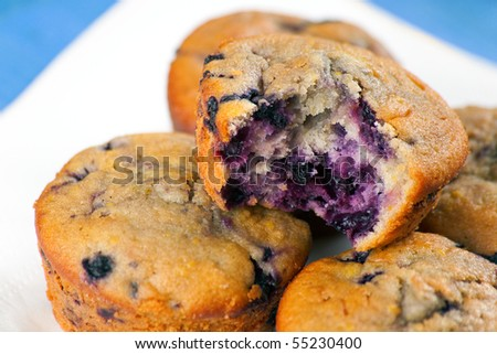Blueberry Muffins on a wooden plate showing the berries inside - stock photo