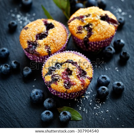 Blueberry muffins with addition of coconut flakes. Delicious dessert - stock photo