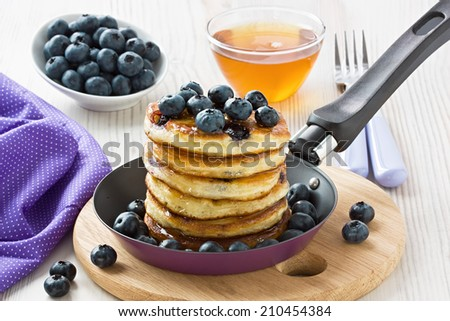 Blueberry pancakes with honey, maple syrup and berries   - stock photo