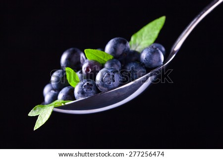 blueberry, ripe berries and green leaves on  black background - stock photo