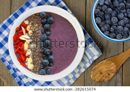 Blueberry smoothie bowl with almonds, goji berries and chia seeds on a wood table with fresh blueberries - stock photo