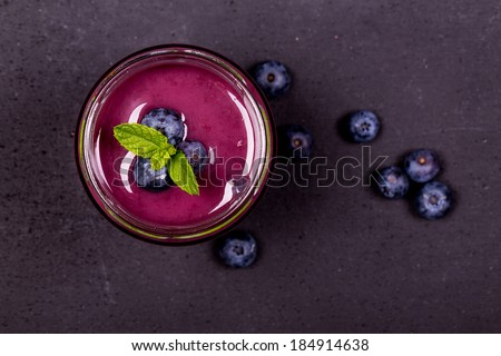 Blueberry smoothie in a glass jar with fresh berries and mint garnish, on a chalk board background - stock photo