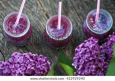 Blueberry smoothie in small glasses on a wooden table - stock photo