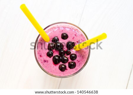 Blueberry smoothie with two straws close up, on white wooden background - stock photo