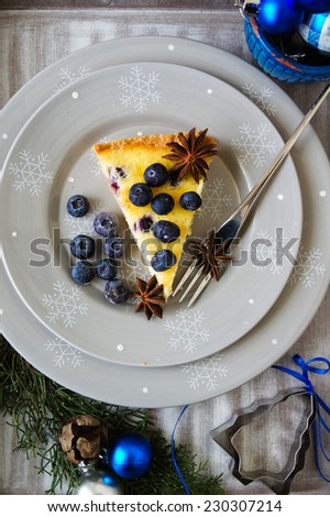 Blueberry tart with anise and cinnamon on the christmas time decorated table - stock photo