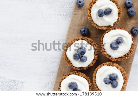 Blueberry tarts on a wooden platter, healthy dessert tart snack - stock photo