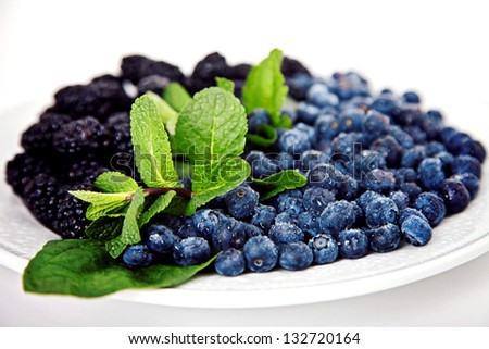Blueberry with mulberry and mint on white plate - stock photo