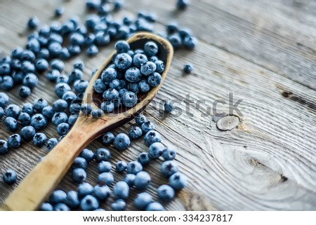 blueberry with wooden spoon on wooden table