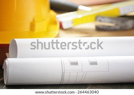 Blueprint rols and helmet - stock photo
