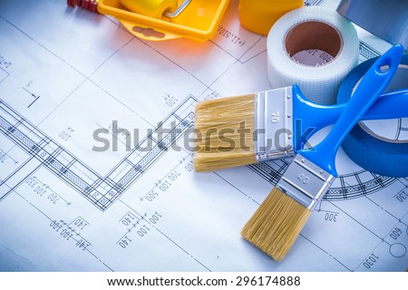 Blueprint with paint roller tray brushes bottle duct tape and wooden meter copy space image construction concept, - stock photo