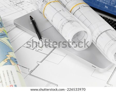 Blueprints and pencil on laptop