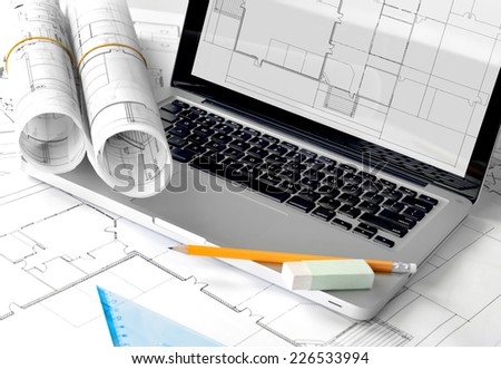 Blueprints and pencil on laptop - stock photo