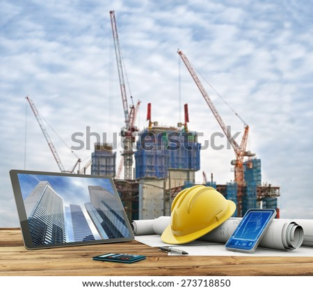 blueprints and safety helmet over a table in construction site - stock photo