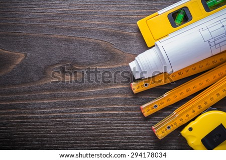 Blueprints construction level tape-measure and wooden meter on vintage wood board maintenance concept. - stock photo