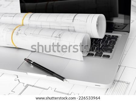 Blueprints, pencil and laptop - stock photo