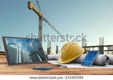 blueprints, safety helmet and computer in construction site - stock photo