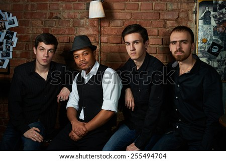 Blues band musicians in nightclub with brick wall - stock photo