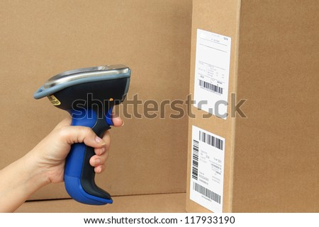 Bluetooth Barcode and QR Code Scanner, showing scan barcode label on the box. - stock photo