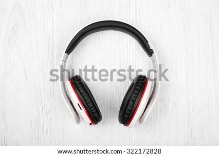 Bluetooth headphones on white wood background - stock photo